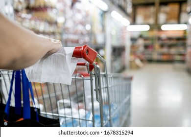 Asian woman with shopping cart,trolley,hand of girl using tissue paper to touch objects instead of hand to avoid contamination of virus,epidemic,outbreak of Covid-19,during the pandemic of Coronavirus