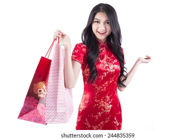 Asian woman shopping happy smiling holding shopping bags a lot. Asian girl shopper isolated on white background dressed in cheongsam.