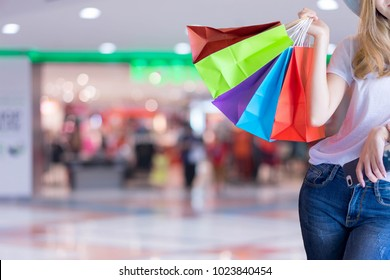 Asian woman shopping holding shopping bag and mobile phone at shopping center. Consumerism, sale and people online concept.