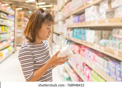 Asian Woman shopping sanitary napkin at the supermarket.
