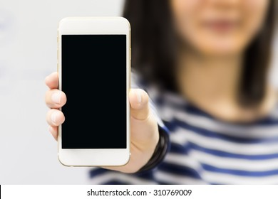 Asian woman show blank smart phone display on a white background. Focus on the hand