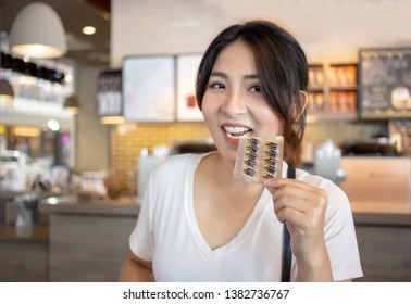 asian woman show canabis pill in coffee shop