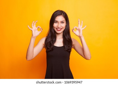 Asian woman show double OK hand sign  and smile on yellow background