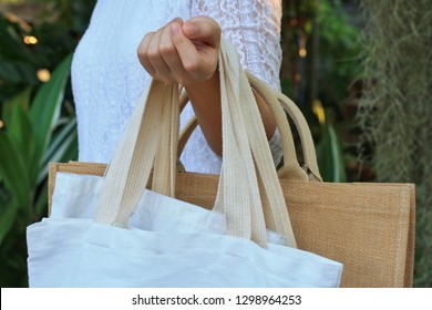 Asian woman show many blank linen nature canvas tote bag with green garden background.Use tote bag for Replacement plastic bag can save the earth.Reduce global warming concept.