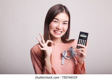Asian woman show OK with calculator on gray background