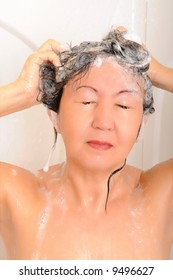 Asian woman showering and washing her hair with shampoo