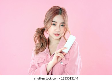 Asian woman showing blank product, jeans jacket clothing, pink background