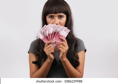 asian woman showing rupiah money thinking for shopping. woman hand showing rupiah Indonesian money for buy.