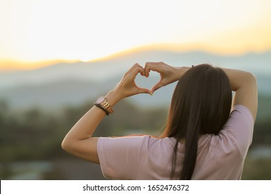 An Asian woman shows a heart symbol to tell her lover on Valentine's Day and the symbol showing love and friendship that has always been. The concept of love and friendship between friends and lovers