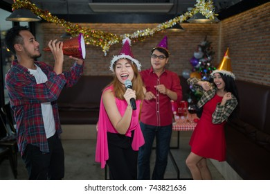 Asian woman singer in santa claus hat with a microphone singing and dancing in Christmas party and friend in restaurant. concept of Xmas party, Christmas party and New year party celebration.