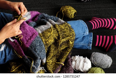Asian woman sit on floor of home to knit woolen blanket for warm in wintertime, knitting is hobby in leisure activity to make handmade gift, photo of woman hand working from top view on day