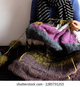 Asian woman sit on floor of home to knit woolen blanket for warm in wintertime, knitting is hobby in leisure activity to make handmade gift, photo of woman hand working from front view on day