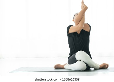 Asian woman sits on floor cover with exercise mat practice yoga eagle pose at home. Clam meditation and relaxation concept. White background copy space.