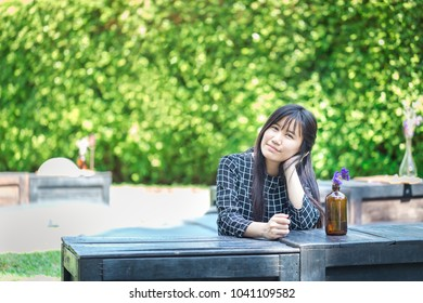 Asian woman sitting at coffee shop in outdoor zone with green plant blur background