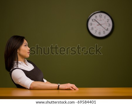 An asian woman sitting at a desk watching the clock