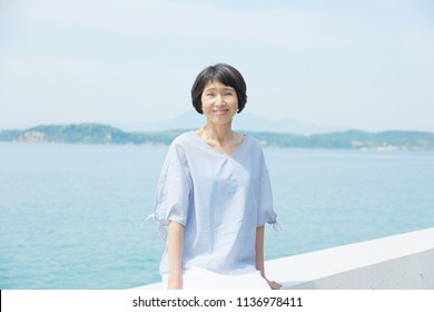 Asian woman sitting down on the breakwater