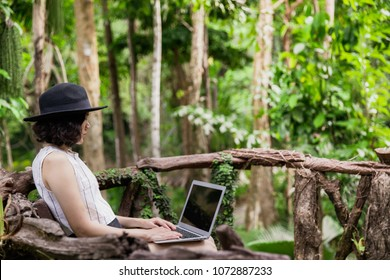 Asian woman sitting in the forest using laptop computer. Girl working on her computer in the wood.