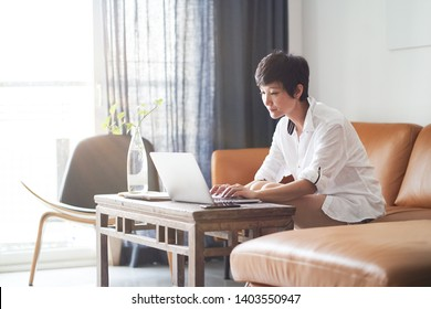 Asian woman sitting in living room working on laptop
