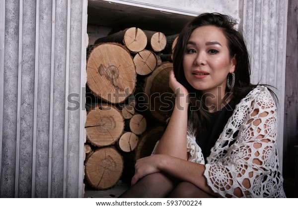 Asian woman sitting near fireplace with shawl on her shoulders.