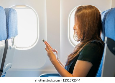 Asian woman sitting on seat in plane cabin and using smartphone, read news from networks via smartphone and wifi on board, young woman sending message on phone.
