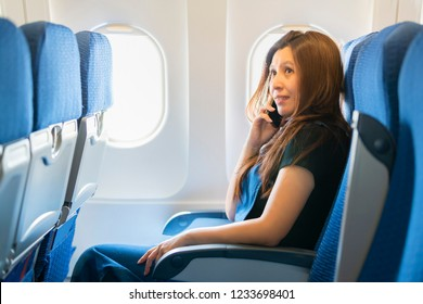 Asian woman sitting on seat in plane cabin near the window and talking on mobile phone.