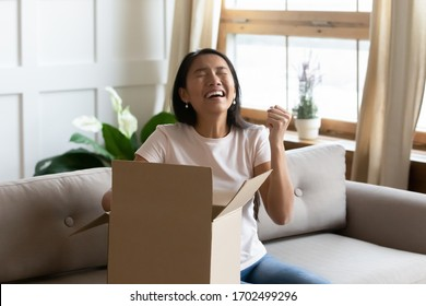 Asian woman sitting on sofa opens delivered parcel feels overjoyed. Excited girl customer unbox cardboard box at home satisfied with great purchase by trusted postal shipping delivery service concept