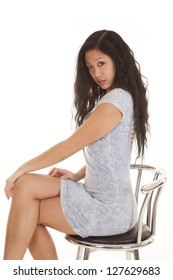 An Asian woman sitting on a stool with a serious expression in her blue dress.