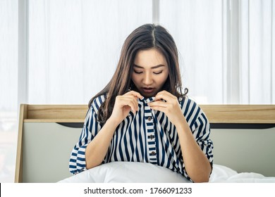 Asian woman sitting on a white bed, she open her shirt and bent down to see her breast size, concept for women who are concerned about the size of the breast