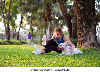 Asian woman sitting and play with her dog after jogging in the morning. dog walking in outdoor green park. enjoy exercise and keep fit with your pet.