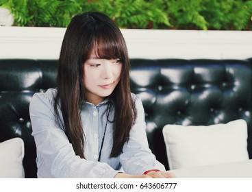 An Asian woman sitting in a Western Restaurant