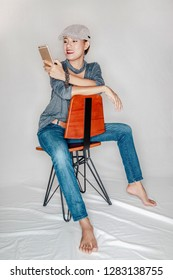 Asian woman sitting in a wooden chair and looking at the phone in a relaxed position.Focus on the face
