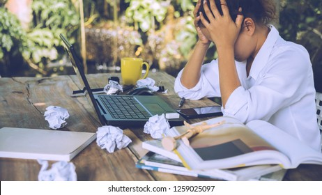 asian woman sitting working at home on vacation. Use working with notebook. Feeling very stressed and headaches with work done.