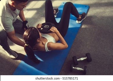 Asian woman are sit-up with added weight on her more and more trainer are there to help.