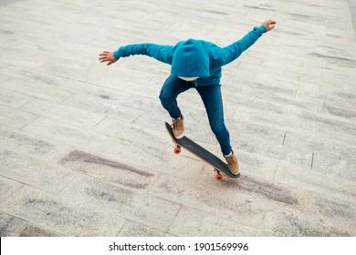 Asian woman skateboarder skateboarding in modern city
