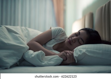 Asian woman sleeping in a bed in a dark bedroom