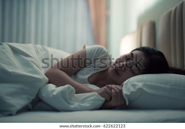 mulher asiática dormir no um cama no um escuro quarto