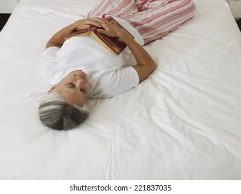 Asian woman sleeping with book
