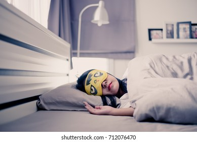 Asian woman sleeping with eye mask on bed  in the morning