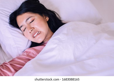 Asian woman sleeping and grinding teeth in bedroom,Female tiredness and stress