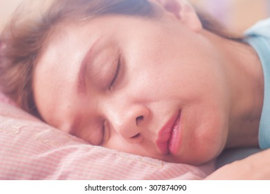 Asian woman sleeping on bed