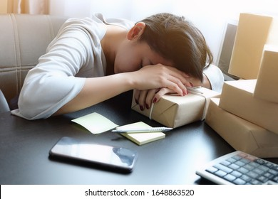 Asian woman sleeping on table, work hard all night until morning with mobile phone, laptop, calculator and many parcel box as trader online sale, package to prepare order of product sent to customer