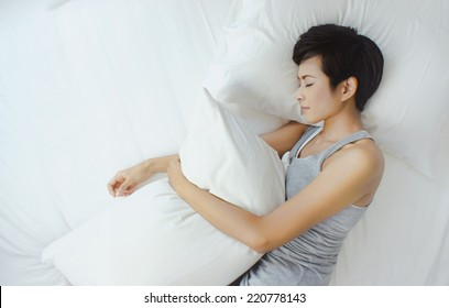Asian woman sleeping in white bed, view from above