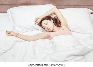 Asian woman sleeps relaxed on a large spacious bed at home or in a hotel