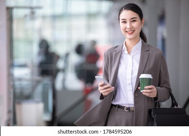 Asian woman with smartphone standing against street blurred building background. Fashion business photo of beautiful girl in casual suite with phone and cup of coffee