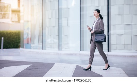 Asian woman with smartphone standing against street blurred building background. Fashion business photo of beautiful girl in casual suite with smart phone.