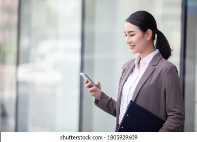 Asian woman with smartphone standing against street blurred building background, Fashion business photo of beautiful girl in casual suite with smart phone.