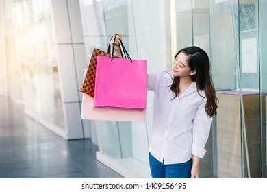 Asian woman smile with shopping bags enjoy in shopping mall