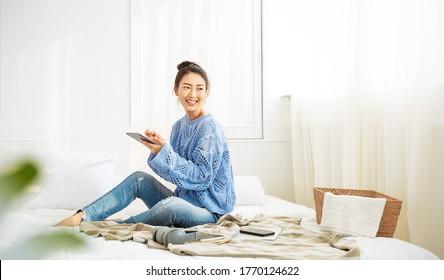 Asiatische Frau mit Lächeln benutzen Tablet Smartphone in blauen Winter Pullover arbeiten zu Hause, Portrait junge Schönheitssaiterin entspannen im Schlafzimmer. Technologie-Menschen verbinden digitale Online-Social-Media-Markt-Banner