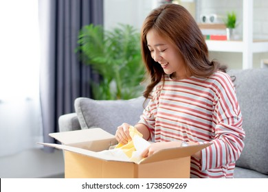 Asian woman smiled and satisfied with the product in the brown box ordered online at home.