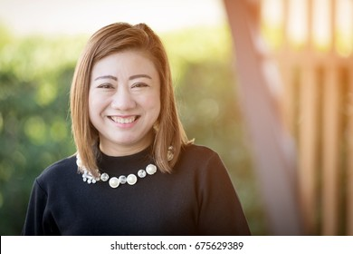 Asian woman smiling happy portrait with sunlight . Beautiful mature middle aged Thailand Asian woman closeup beauty portrait